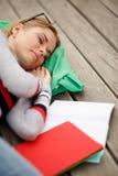 Lo studente dorme con il cortile dell'istituto universitario dei libri Immagine Stock
