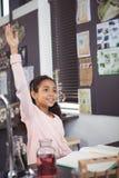 Lo studente elementare sorridente con la mano si è alzato all'aula Fotografie Stock