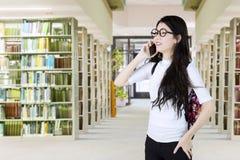 Lo studente fa una telefonata in biblioteca Fotografia Stock