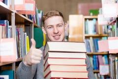Lo studente felice con il mucchio prenota la mostra dei pollici su nella biblioteca di istituto universitario Fotografia Stock Libera da Diritti