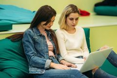 Lo studente felice ha un'università di irrompere Diverta mentre per mezzo del telefono, della compressa e del computer portatile Immagini Stock Libere da Diritti