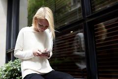 Lo studente femminile dei pantaloni a vita bassa che per mezzo del telefono cellulare per si collega alla radio all'aperto Immagini Stock