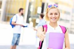 Lo studente grazioso che mostra okay firma dentro la città universitaria Fotografia Stock