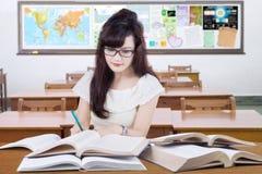 Lo studente grazioso impara con i libri nella classe Fotografie Stock