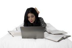 Lo studente grazioso impara con il computer portatile sul letto Fotografia Stock Libera da Diritti