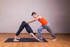 Lo studente guidante dell'istruttore di yoga esegue la posa orientata verso il basso del cane Fotografia Stock