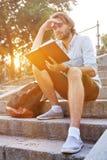 Lo studente ha letto un libro che si siede sulle scale in città universitaria Immagine Stock