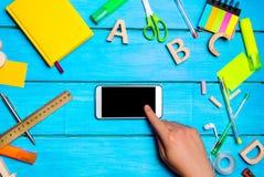 Lo studente indica il telefono, il diario digitale o il libro elettronico, riluttanza per imparare, rifornimenti di scuola su un  immagini stock libere da diritti