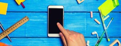 Lo studente indica il telefono, il diario digitale o il libro elettronico, riluttanza per imparare, rifornimenti di scuola su un  fotografie stock