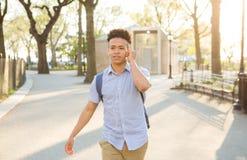 Lo studente ispano con capelli ricci cammina sulla città universitaria allineata albero Fotografie Stock