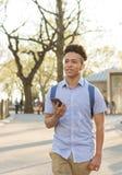 Lo studente ispano con capelli ricci cammina sulla città universitaria allineata albero Fotografie Stock Libere da Diritti