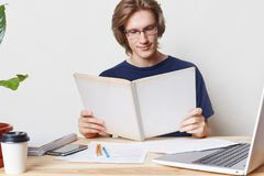 Lo studente maschio alla moda lavorante duro astuto indossa gli occhiali, ha sguardo fisso attento in libro, legge la letteratura Fotografie Stock