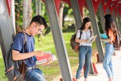 Lo studente maschio legge sulla città universitaria Fotografia Stock