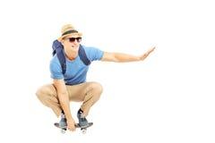 Lo studente maschio sorridente con lo zaino che pattina su un pattino imbarca Fotografie Stock