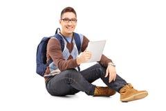 Lo studente maschio sorridente con lo zaino ha messo su un pavimento che tiene una t Fotografia Stock Libera da Diritti