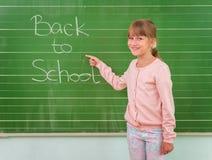 Lo studente mostra un bordo con l'iscrizione: Di nuovo alla scuola Immagini Stock Libere da Diritti