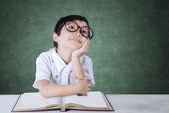 Lo studente pensieroso della scuola primaria si siede nella classe Fotografia Stock