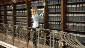Lo studente prende il libro dagli scaffali nella biblioteca stock footage