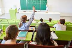 Lo studente solleva la mano e risponde alla domanda Immagine Stock