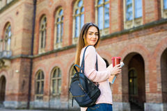 Lo studente sorridente con la borsa e porta via il caffè nel giardino della città universitaria immagini stock