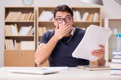 Lo studente spaventato con lavoro di ufficio in biblioteca Immagine Stock