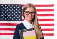 Lo studente sta imparando l'inglese come lingua straniera sul fondo della bandiera americana Immagini Stock