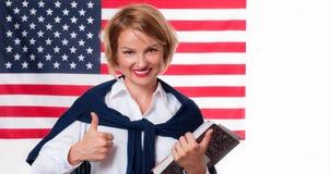Lo studente sta imparando l'inglese come lingua straniera sul fondo della bandiera americana Immagine Stock Libera da Diritti