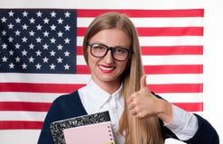 Lo studente sta imparando l'inglese come lingua straniera sul fondo della bandiera americana Fotografia Stock Libera da Diritti