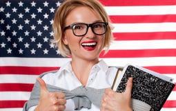 Lo studente sta imparando l'inglese come lingua straniera sul fondo della bandiera americana Fotografie Stock Libere da Diritti