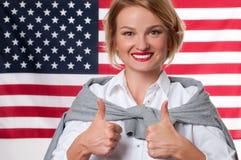 Lo studente sta imparando l'inglese come lingua straniera sul fondo della bandiera americana Fotografia Stock