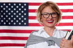 Lo studente sta imparando l'inglese come lingua straniera sul fondo della bandiera americana Immagine Stock