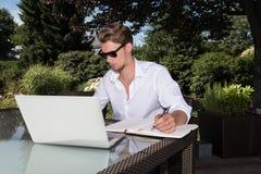 Lo studente sta lavorando con il computer portatile ed il libro nel giardino Immagine Stock