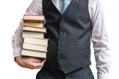 Lo studente sta tenendo molti libri in mani Isolato su priorità bassa bianca Immagine Stock