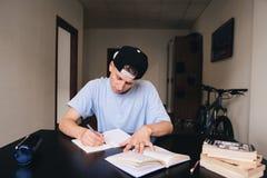 Lo studente studia a casa lavoro Un teenager con uno sguardo da vicino scrive il testo al suo taccuino Fotografie Stock