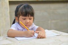Lo studente sveglio asiatico fa il compito Fotografia Stock