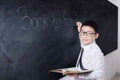 Lo studente tiene il libro con testo di nuovo alla scuola Fotografie Stock