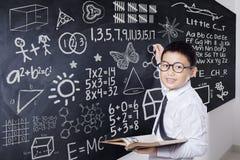 Lo studente tiene il libro e scrive la formula Immagine Stock