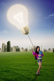 Lo studente tiene la lampadina luminosa al campo Immagine Stock