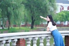 Lo studente universitario cinese asiatico gode del tempo libero alla città universitaria Fotografie Stock Libere da Diritti