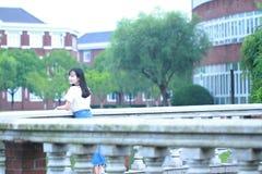 Lo studente universitario cinese asiatico gode del tempo libero alla città universitaria Fotografia Stock Libera da Diritti