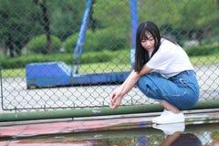 Lo studente universitario cinese asiatico gode del tempo libero alla città universitaria Immagini Stock