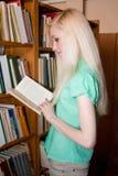 Lo studente universitario femminile ha letto il libro nella libreria Immagine Stock Libera da Diritti