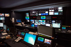 Lo studio di notizie di trasmissione televisiva con molti schermi di computer ed i pannelli di controllo per aria in tensione han