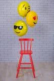 Lo studio grigio dell'appartamento con la sedia, muro di mattoni, dettagli gialli balloons la sedia di rosso di emoji Fotografia Stock