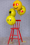 Lo studio grigio dell'appartamento con la sedia, muro di mattoni, dettagli gialli balloons la sedia di rosso di emoji Fotografia Stock Libera da Diritti
