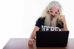 Lo studio ha sparato dell'uomo barbuto senior del nerd che sembra arrabbiato mentre usando immagini stock