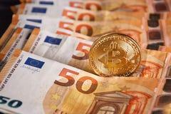 Lo studio ha sparato della moneta dorata fisica del bitcoin su 50 euro banconote delle fatture Bitcoin è una valuta cripto del bl Fotografie Stock