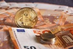 Lo studio ha sparato della moneta dorata fisica del bitcoin su 50 euro banconote delle fatture Bitcoin è una valuta cripto del bl Immagini Stock