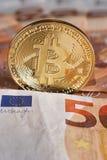 Lo studio ha sparato della moneta dorata fisica del bitcoin su 50 euro banconote delle fatture Bitcoin è una valuta cripto del bl Fotografia Stock