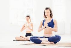 Lo studio ha sparato delle giovani donne che fanno gli esercizi di yoga su fondo bianco Fotografie Stock